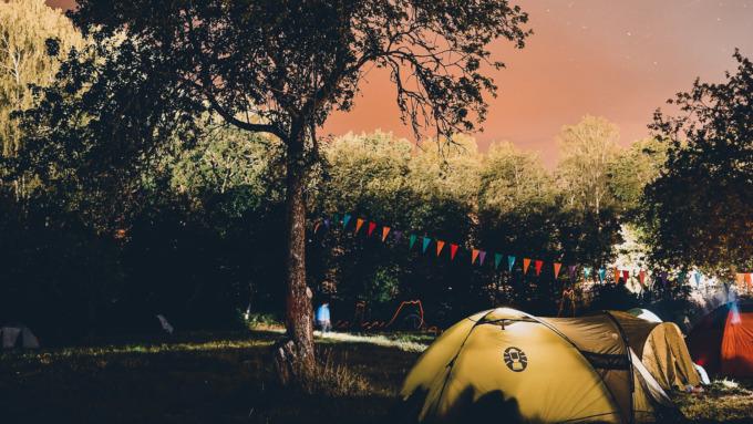 Campingplatz mit erleuchteten Zelten und Wimpelkette zwischen Laubbäumen.