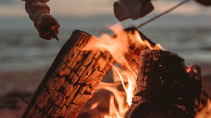 Stockbrot wird auf einem Lagerfeuer gegrillt.